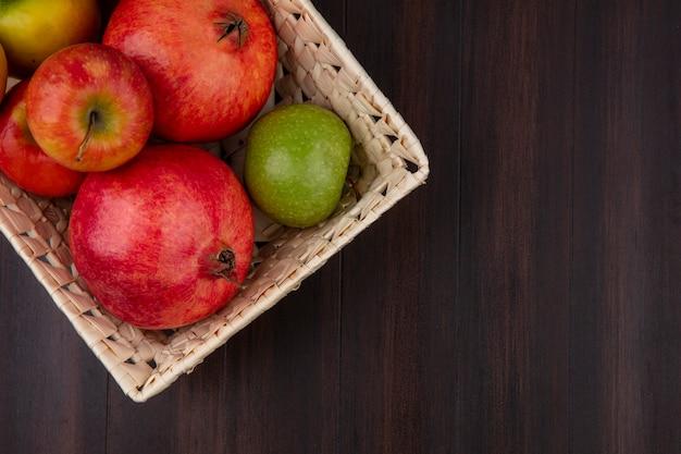 Vista superior da romã com maçãs coloridas em uma cesta sobre uma superfície de madeira