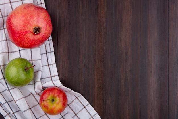 Vista superior da romã com maçãs em uma toalha quadriculada branca sobre uma superfície de madeira
