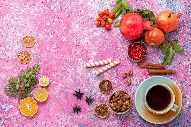 Vista superior da romã fresca com folhas verdes e uma xícara de chá na superfície rosa claro