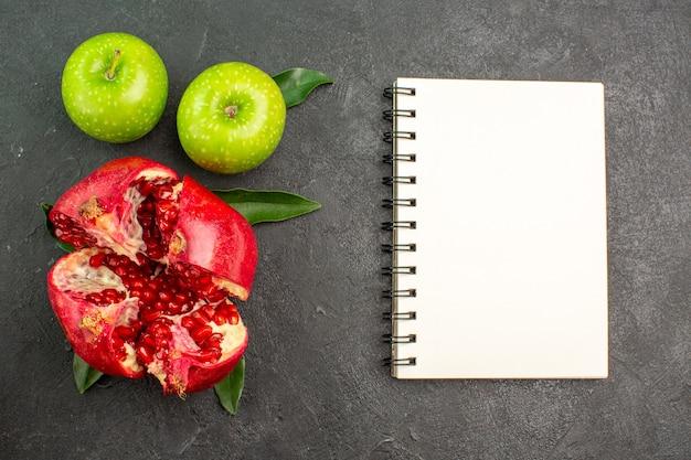 Vista superior da romã fresca com maçãs verdes e bloco de notas na superfície escura da cor de frutas maduras