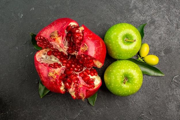 Vista superior da romã fresca com maçãs verdes na superfície escura, cor de frutas maduras