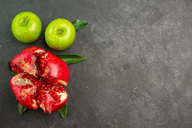 Vista superior da romã fresca com maçãs verdes na superfície escura de cor de frutas maduras