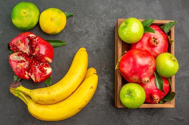 Vista superior da romã fresca com tangerinas e bananas na superfície escura, cor de fruta madura