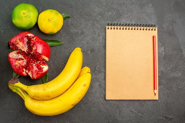 Vista superior da romã fresca com tangerinas e bananas no chão escuro de cor de frutas maduras