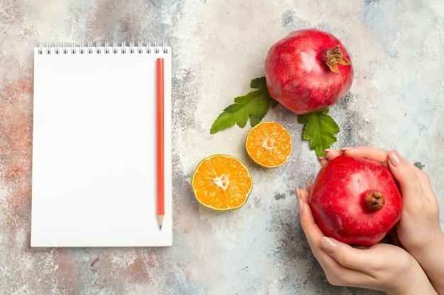 Vista superior da romã vermelha em fatias de limão à mão feminina lápis vermelho no caderno na superfície nua