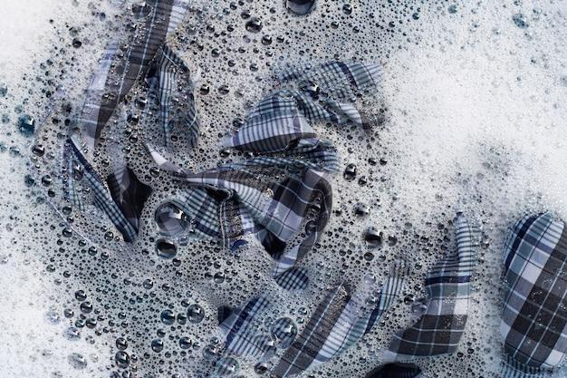 Vista superior da roupa embebida em água com detergente em pó. conceito de lavanderia