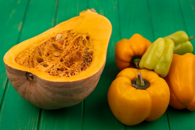 Vista superior da saborosa abóbora laranja com suas sementes e pimentões isolados em uma parede de madeira verde
