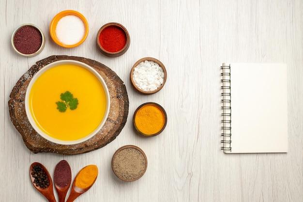 Vista superior da saborosa sopa de abóbora com diferentes temperos em branco