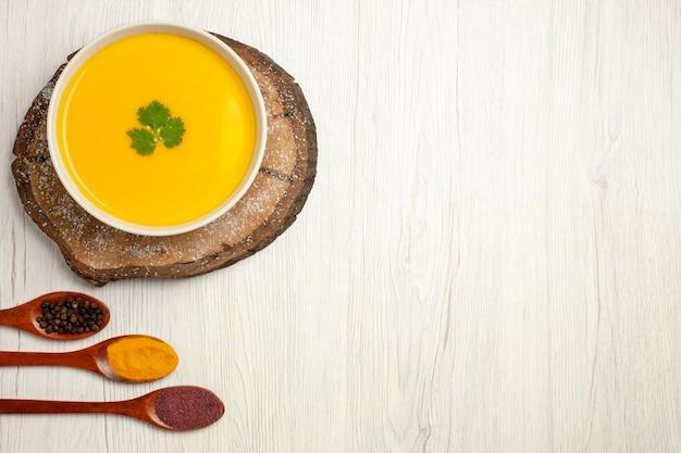 Vista superior da saborosa sopa de abóbora com temperos em branco
