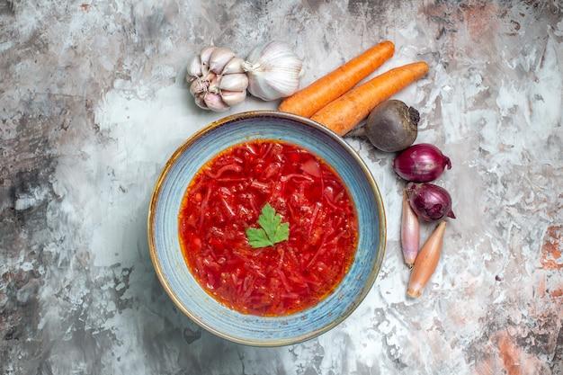 Vista superior da saborosa sopa de beterraba ucraniana com legumes frescos em superfície escura