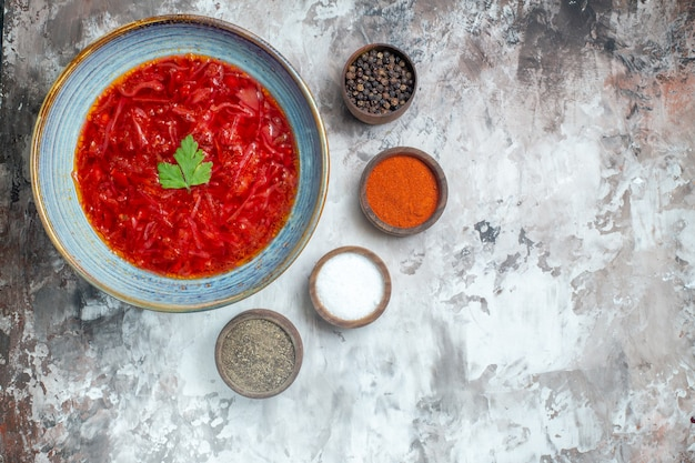 Vista superior da saborosa sopa de beterraba ucraniana com temperos na superfície branca