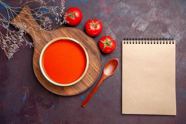 Vista superior da saborosa sopa de tomate com tomates frescos no escuro