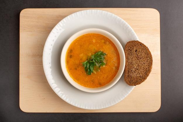 Vista superior da saborosa sopa de vegetais dentro do prato com pão de forma na superfície escura
