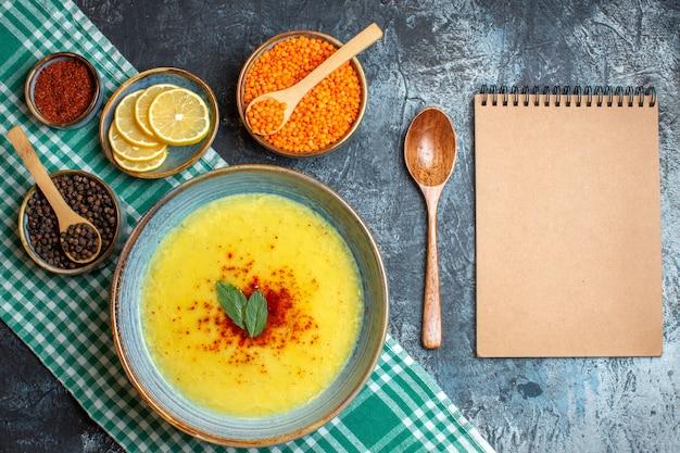 Vista superior da saborosa sopa servida com hortelã e pimenta em um pano verde descascado