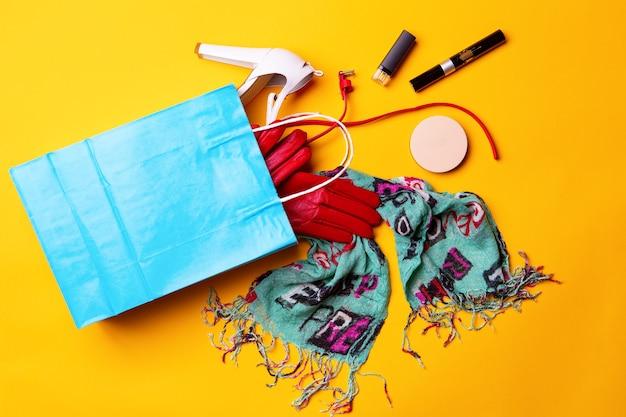 Vista superior da sacola de compras azul com sapatos elegantes, lenço, cinto vermelho e luvas e cosméticos em amarelo