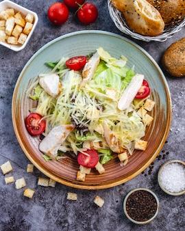 Vista superior da salada caesar de frango com recheio de pão de tomate cereja alface e parmesão