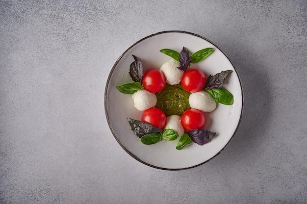 Vista superior da salada caprese italiana com tomates maduros, manjericão fresco e queijo mussarela em prato branco