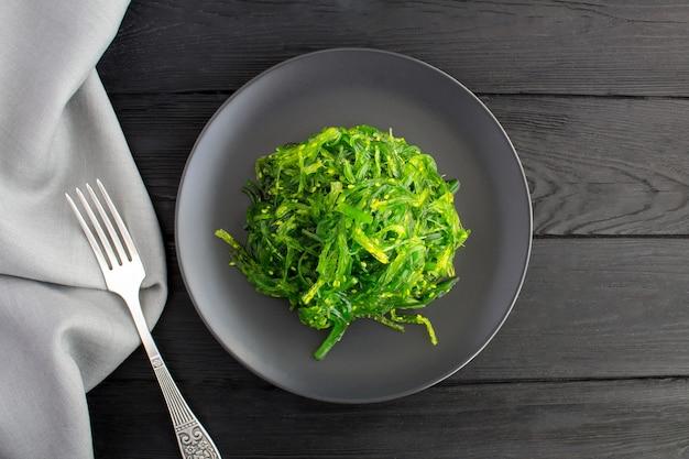 Vista superior da salada com algas e gergelim no prato escuro