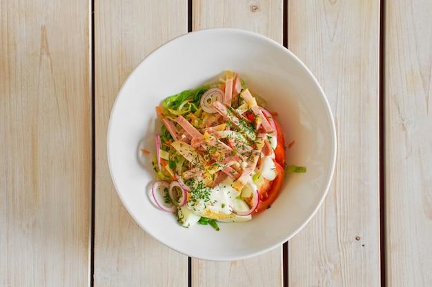 Vista superior da salada com presunto, tomate, cebola roxa e ovo