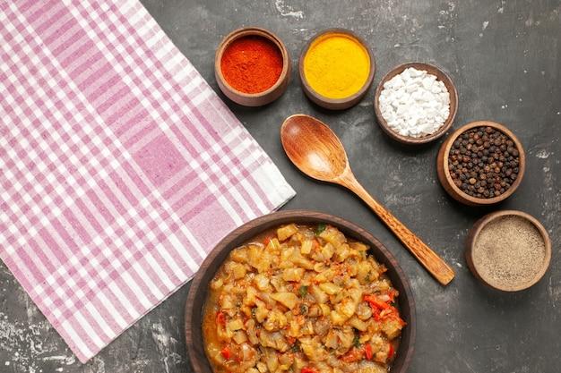 Vista superior da salada de berinjela assada em uma tigela, colher de pau, diferentes especiarias em tigelas e toalha de cozinha na superfície escura