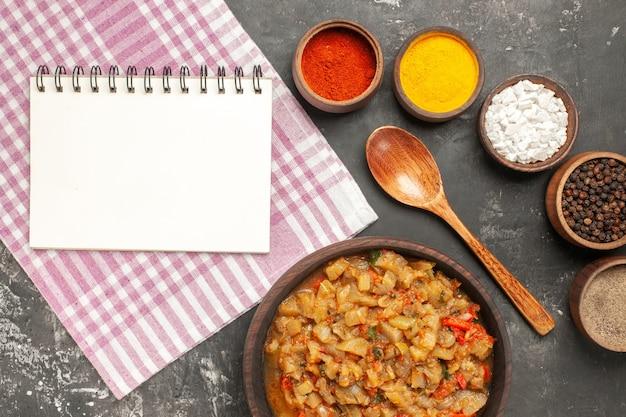 Vista superior da salada de berinjela assada em uma tigela, colher de pau, especiarias diferentes em tigelas, um caderno na superfície escura