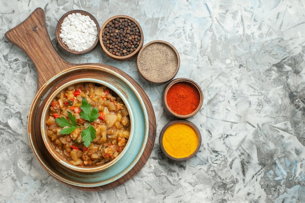 Vista superior da salada de berinjela assada em uma tigela e diferentes especiarias em tigelas na superfície cinza Foto gratuita