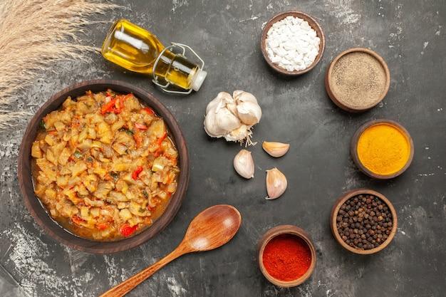 Vista superior da salada de berinjela assada em uma tigela, garrafa de óleo, alho, colher de pau, especiarias diferentes na superfície escura