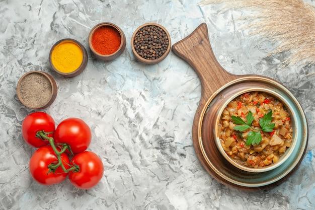 Vista superior da salada de berinjela assada em uma tigela na tábua de cortar especiarias diferentes em tigelas um caderno de tomates na superfície cinza