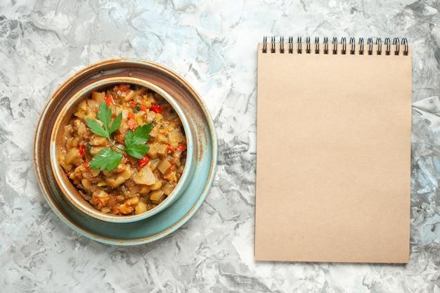 Vista superior da salada de berinjela assada em uma tigela, um caderno na superfície cinza