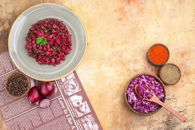 Vista superior da salada de beterraba como uma mistura de vegetais cozidos no vapor, como pimenta-do-reino, cebola vermelha, pimenta moída, cúrcuma e repolho roxo, em um prato de cerâmica cinza sobre um fundo claro
