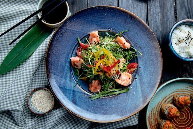 Vista superior da salada de camarão com pimentão e rúcula em um prato na madeira