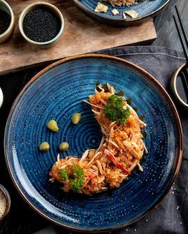 Vista superior da salada de caranguejo com legumes e wasabi em um prato e molho de soja no preto