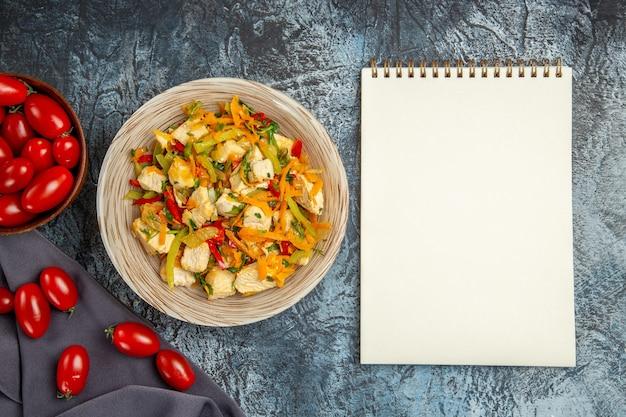 Vista superior da salada de frango com vegetais e tomates na mesa iluminada