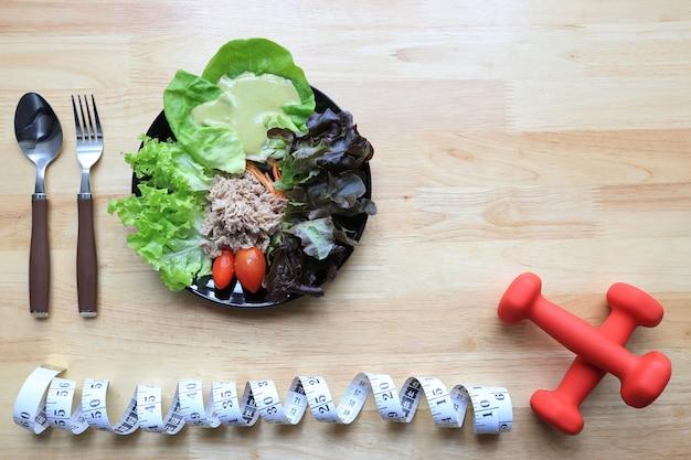 Vista superior da salada de legumes com dumbells e fita métrica na madeira escura