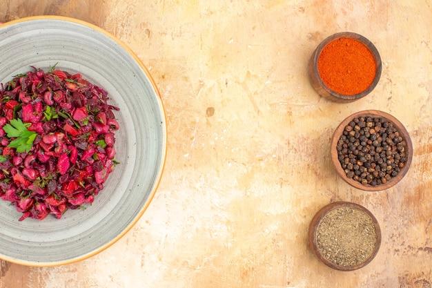 Vista superior da salada de legumes com folhas de salsa com pimenta preta, pimenta do reino moída e açafrão em uma mesa de madeira com espaço para texto no meio