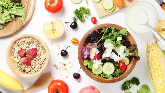 Vista superior da salada de legumes mistos, muesli e frutas frescas no fundo branco