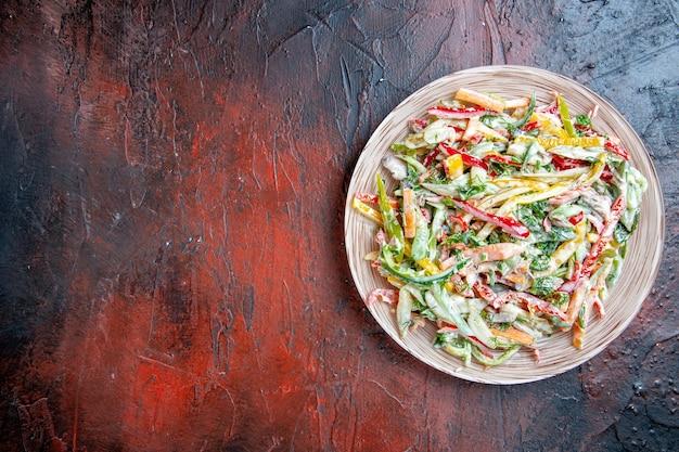 Vista superior da salada de legumes no prato na mesa vermelha escura com lugar grátis