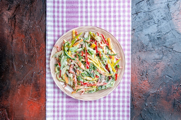 Vista superior da salada de legumes no prato no guardanapo no lugar de cópia da mesa vermelho escuro