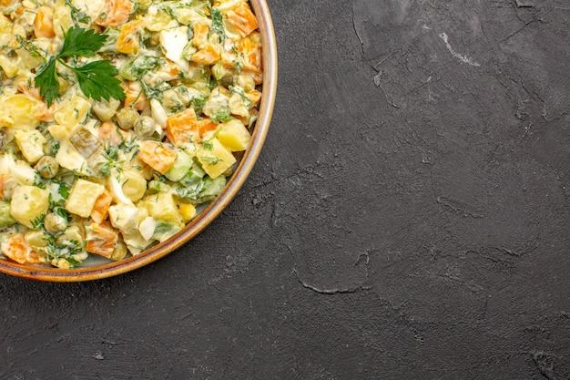 Vista superior da salada de maionese com diferentes vegetais em superfície escura
