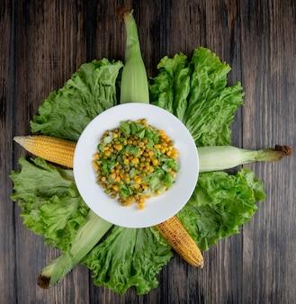 Vista superior da salada de milho com alface e ervilha verde com grãos na superfície de madeira