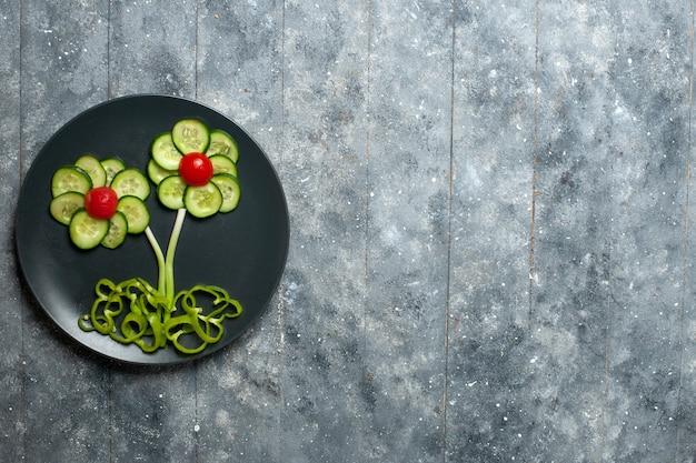 Vista superior da salada de pepinos frescos com flores na mesa cinza