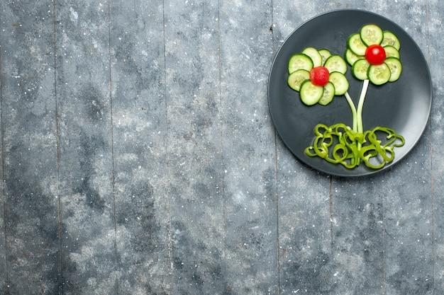 Vista superior da salada de pepinos frescos com flores projetadas no espaço cinza