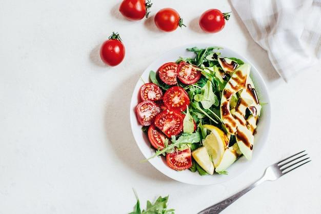 Vista superior da salada de tomate rúcula e limão com abacate em chapa branca sobre fundo claro