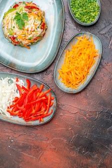 Vista superior da salada de vegetais com fatias de repolho de cenoura e pimentão em uma mesa escura