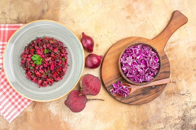 Vista superior da salada de vegetais com folhas verdes com beterraba, cebola roxa e tigela de repolho picado em um fundo de madeira com espaço para texto