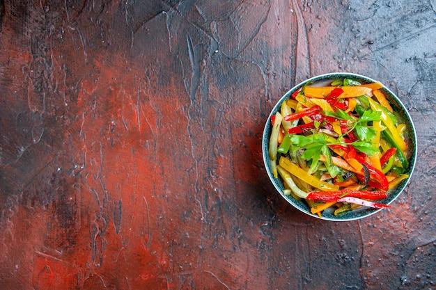 Vista superior da salada de vegetais em uma tigela na mesa vermelha escura com espaço livre