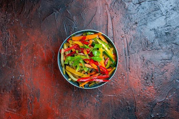 Vista superior da salada de vegetais em uma tigela no espaço livre da mesa vermelha escura
