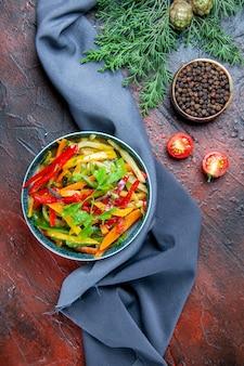 Vista superior da salada de vegetais em uma tigela pimenta preta ramo de abeto xale azul ultramar na mesa vermelho escuro