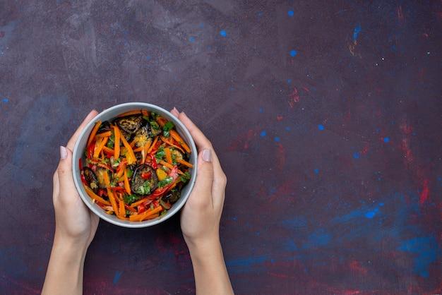 Vista superior da salada de vegetais fatiada dentro do prato, segurando por uma mulher na mesa escura