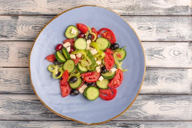 Vista superior da salada de vegetais frescos com pepinos fatiados, tomates e azeitona dentro do prato na superfície cinza cor de refeição de salada de vegetais